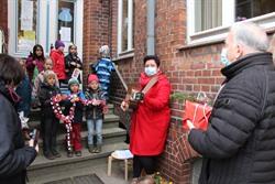 Bürgermeister Eduard Kolle tauscht mit den Kindern der Kita Marienplatz Süßigkeiten gegen selbstgebastelten Baumschmuck. Foto: Hansestadt Lüneburg
