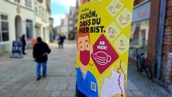 Auf Maskenpflicht und weitere Infektionsschutz-Regeln weisen die neuen freundlichen Plakate in der Innenstadt hin. Foto: Hansestadt Lüneburg